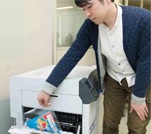 """高堀先生正在打印""""脆脆冰激凌""""的设计样品。C941dn的购入,大幅削减了样品制作的时间。"""